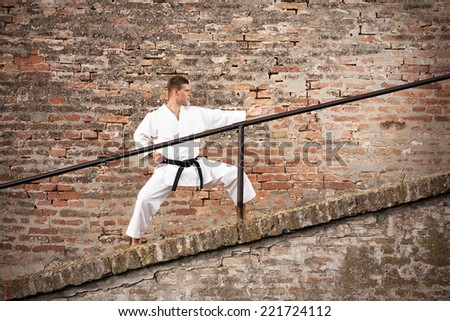 Young man in fighting stance in front of a brick wall - stock photo