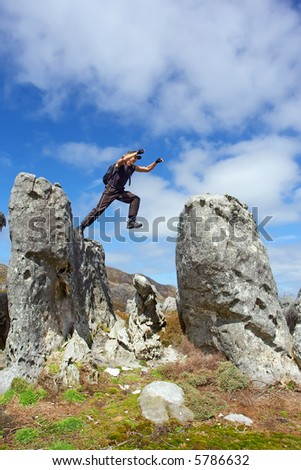 Young man in flee from one rock to another - low angle, against sky. Shot in Hottentots-Holland Mountains nature reserve, near Grabouw, Western Cape, South Africa. - stock photo