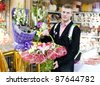 Young man in flower shop - stock photo