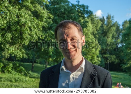 Young man in formal outfit looking with smile in camera, outdoors on the green background. Business man in a green zone or park. An image for topics of finance and business. - stock photo