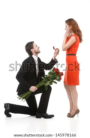 Young man in full suit standing on one knee and making a proposal to his girlfriend against white background - stock photo