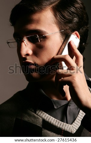 Young man in glasses calling by mobile phone
