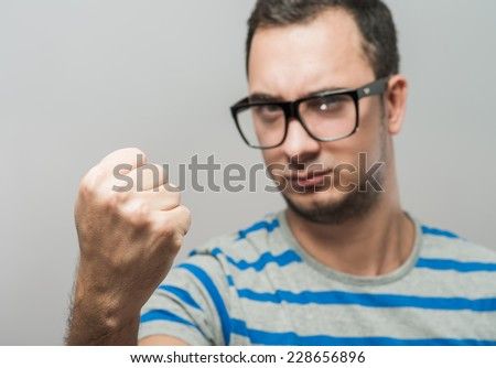 young man in glasses showing a fist - stock photo