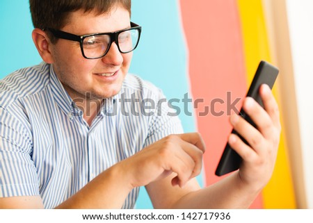 young man in glasses uses a digital tablet - stock photo