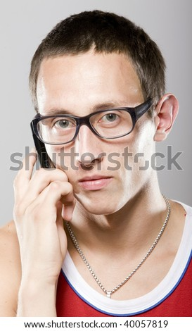 young man in glasses with mobile phone in red sports shirt - stock photo