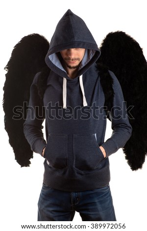 young man in gray jacket and blue jeans with hood thrown over his head standing with his hands in his pockets and on the back with black wings