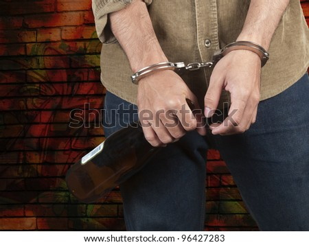Young man in handcuffs and beer bottle stands in front of brick wall - stock photo