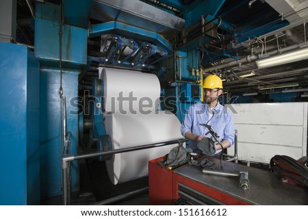 Young man in hardhat working in newspaper factory - stock photo