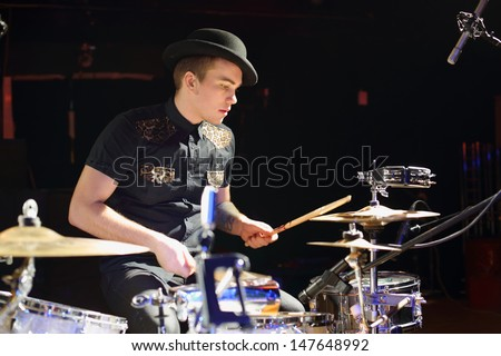 Young man in hat and black shirt plays drum set in night club. - stock photo