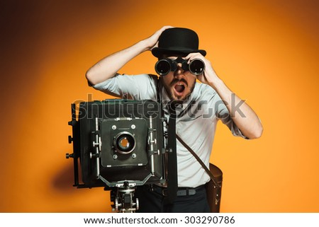 Young man in hat as photographer with retro camera looking through binoculars on an orange background - stock photo