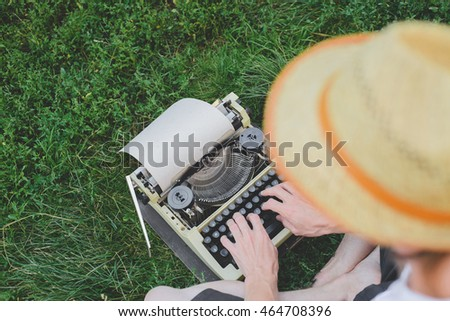 young man in hat is typing on typewriter