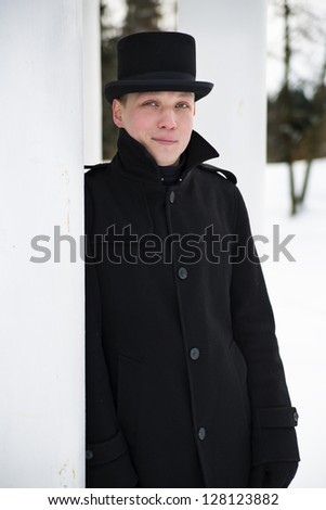 Young man in hat relies on white column