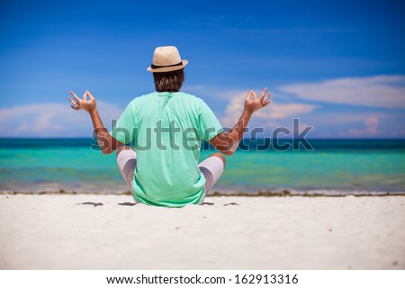 Young man in hat sitting in the lotus position on white sand beach