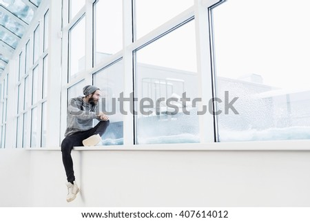 Young man in hat sitting on window sill and looking away sadly