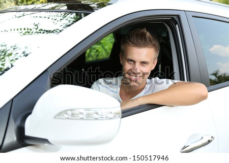 Young man in his new car - stock photo