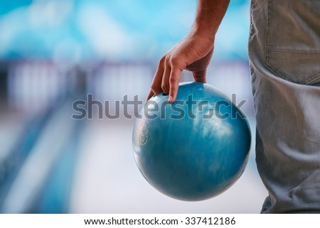 Young man in jeans holding bowling ball - stock photo