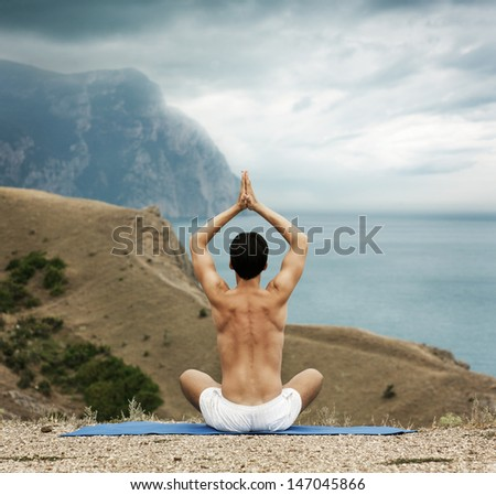 Young Man in Lotus Position near the Ocean. Rear View. - stock photo