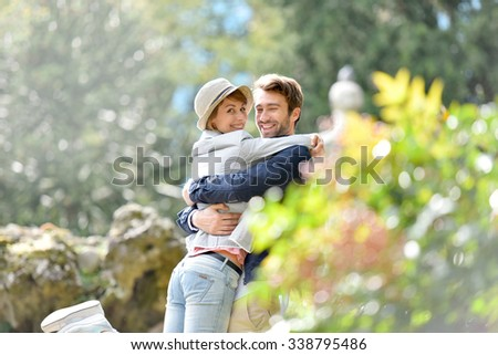 Young man in love lifting his girlfriend in arms