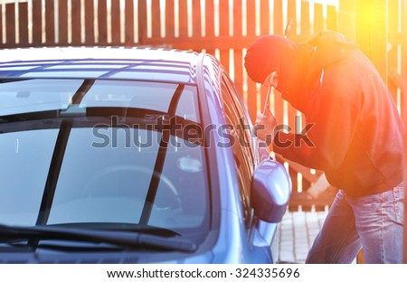 Young man in mask trying to steal a car - stock photo
