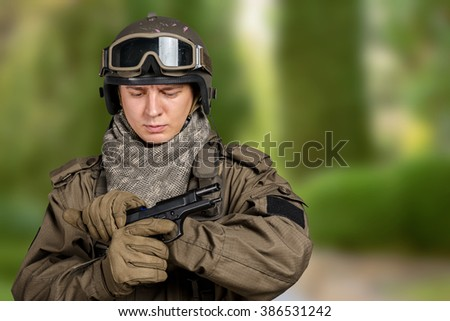 Young man in military uniform checking revolver gun