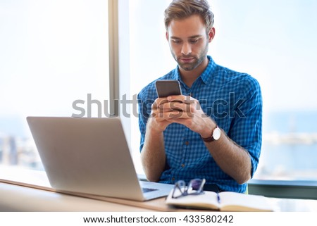 Young man in modern office with his laptop open in front of him, and a large window behind, typing a message on his mobile phone - stock photo