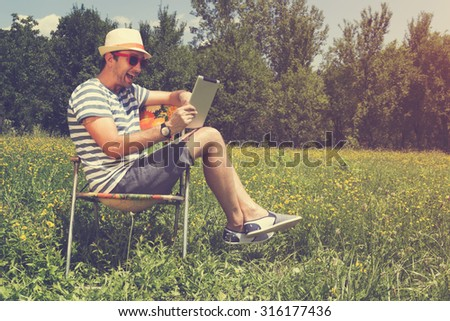 Young man in nature with tablet.