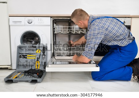 Young Man In Overall With Toolbox Repairing Dishwasher