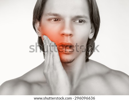 Young man in pain is having a toothache isolated on white background - stock photo