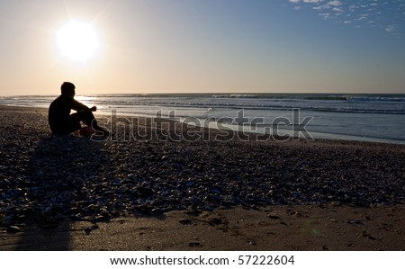 Young man in pensive mood sitting alone on an empty beach