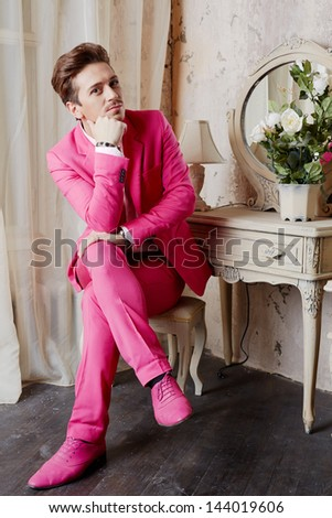 Young man in pink suit and shoes sits on chair with crossed legs and propping chin with his hand - stock photo