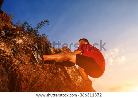 Young man in red shirt climbing on a wall - stock photo