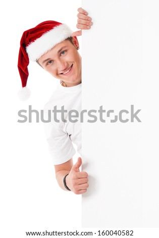 Young man in Santa Claus hat behind white board with space for text over white background - stock photo