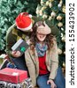Young man in Santa hat surprising woman with Christmas presents in store - stock photo