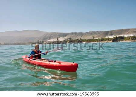 Young man in sea kayak against mountains. Shot in Hermanus during the whale watching season, Western Cape, South Africa. - stock photo