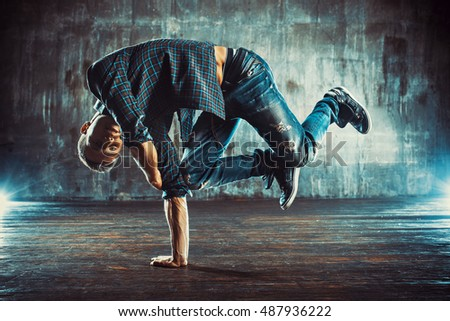 Young man in shirt and jeans break dancing on old wall background