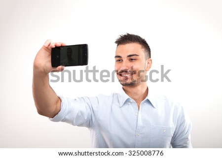 Young man in shirt holding mobile phone and making photo of himself while standing against background - stock photo
