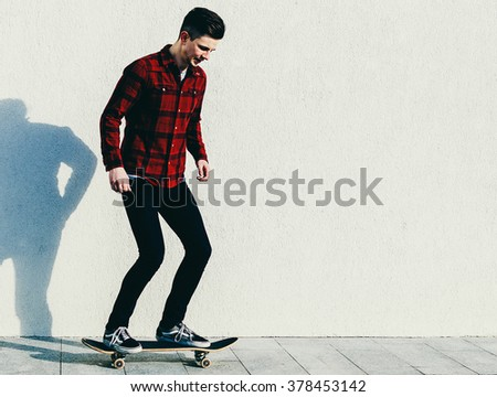 Young man in shirt on the skateboard on the city street - stock photo