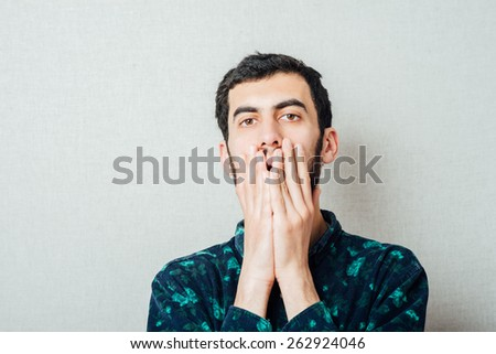 young man in shock with hands on face - stock photo