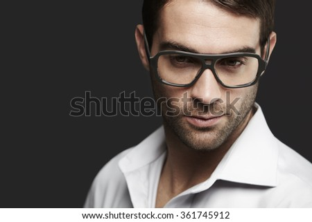Young man in spectacles looking away