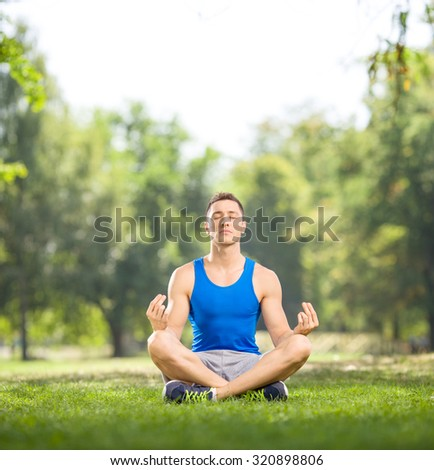 Young man in sportswear practicing yoga seated on grass in a park on a beautiful summer day shot with tilt and shift lens