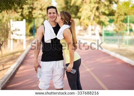 Young man in sporty outfit getting a kiss on the cheek by his girlfriend after exercising together - stock photo