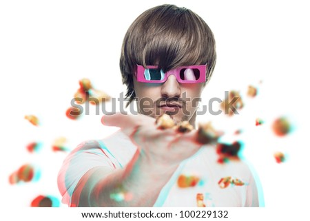 young man in stereo glasses throwing popcorn at the viewer 3d movie concept - stock photo