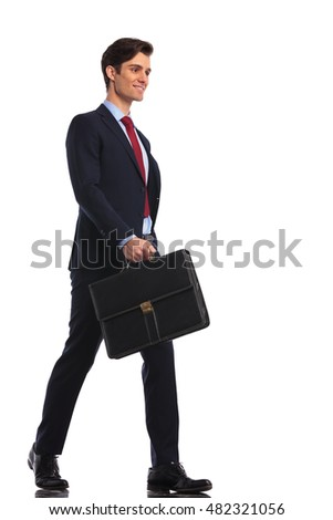 young man in suit and tie laughing while walking with briefcase on white bakground