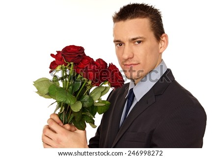 Young man in suit holding flowers of roses