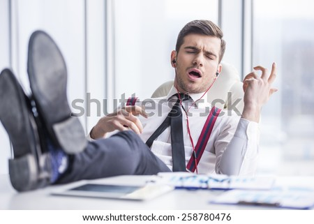 Young man in suit is listening music in headphone in office. - stock photo