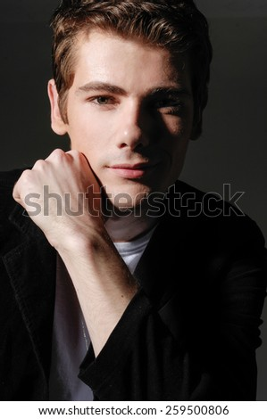 Young man in suit posing �black background - stock photo