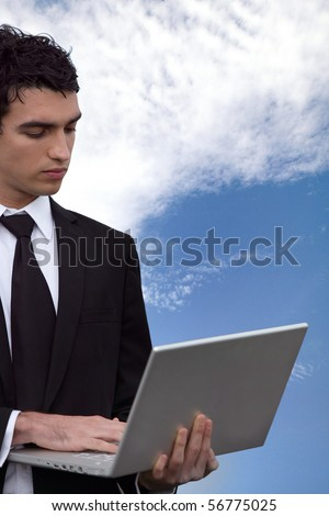 Young man in suit with a laptop computer