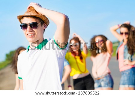 young man in sunglasses, a hat holds a hand on a background of blue sky and friends - stock photo