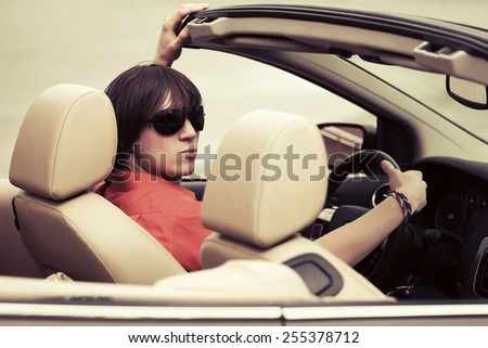 Young man in sunglasses driving a convertible car - stock photo