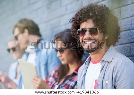 Young man in sunglasses smiling at camera while friends using digital tablet in background - stock photo
